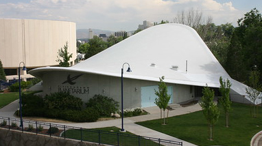 An exterior of the Fleischmann Planetarium and Science Center, a building with a parabolic white roof, walkways and trees surrounding the building.