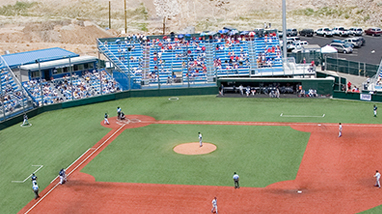Spectators sit in blue stands at the William Peccole Park, a baseball field with green infield and dirt base paths, on the campus of the University of Nevada, Reno.