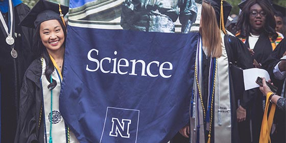 Female student in graduation attire holding College of Science flag.